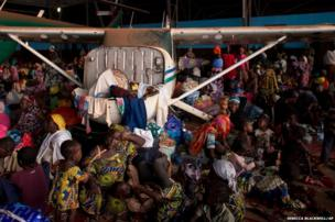 Chadians waiting for evacuation flights settle in for the night inside an airport hangar in Bangui, Central African Republic