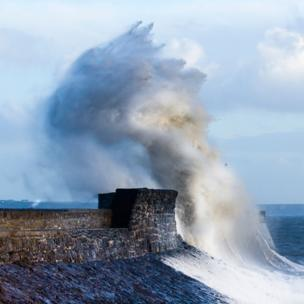 Porthcawl lighthouse pounded by a wave