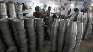 Employees work inside a steel bucket manufacturing unit at an industrial area on the outskirts of the western Indian city of Ahmedabad