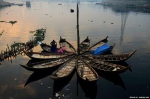 A Bangladeshi boatman tidies up his bedding after waking up in the early morning in Dhaka