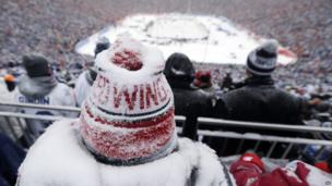 A Detroit Red Wings fan, coated with snow, watches during the third period of the Winter Classic outdoor NHL hockey game against the Toronto Maple Leafs at Michigan Stadium in Ann Arbor, Mich., Wednesday, Jan. 1, 2014.