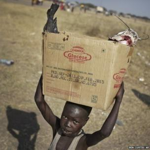 A displaced boy carries a fish, caught from the nearby Nile river