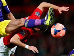 Manchester United's Javier Hernandez (red shirt) is tackled by Swansea City's Chico Flores