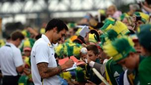Australian cricketer Mitchell Johnson signs autographs during a ceremony to celebrate Australia's victory over England in the Ashes Test series at the Sydney Opera House on 7 January 2014