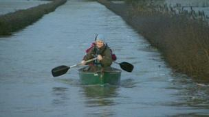 David and Tracey Bradley in their canoe on a flooded Somerset Levels. Still from BBC News Channel