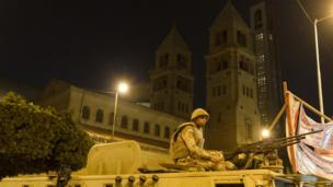 soldier on top of tank outside the al-Abasseya Cathedral in Cairo