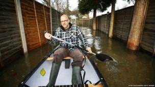 Ian Berry paddles a canoe along his driveway after the River Thames flooded in Chertsey