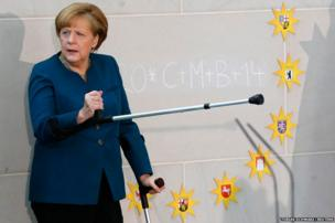 German Chancellor Angela Merkel gestures with a crutch as she meets carols singers during a reception at the Chancellery in Berlin
