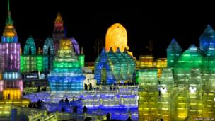 People tour ice sculptures on display during the Harbin International Ice and Snow Sculpture Festival