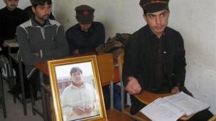 Pakistani students sit next to a picture of 17-year-old classmate Aitzaz Hasan, in Hangu, Pakistan, Jan. 10, 2014.