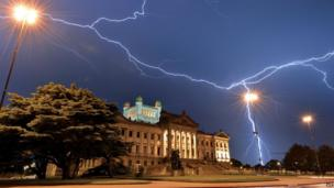 Lightning streaks across the sky of Montevideo, over the Legislative Palace - seat of the Uruguayan Government - during a thunderstorm early on January 10, 2014.
