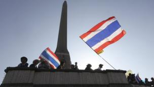 Anti-government protesters with national flags take positions at a rally at Victory Monument on 13 January 2014