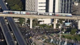 An elevated train passes over an intersection that is being blocked by anti-government protesters in Bangkok on 13 January 2014