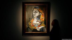 A worker poses with Pablo Picasso's Femme au costume turc dans un fauteuil painting