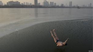 A 74-year-old man runs and jumps into a half frozen river during his afternoon exercises in Taiyuan, Shanxi province, 14 January 2014