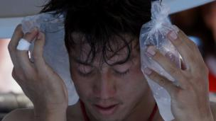 Kei Nishikori of Japan holds an ice pack to his face