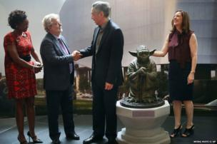 Singapore's Prime Minister Lee Hsien Loong (centre) shakes hands with George Lucas as the President of Lucasfilm, Kathleen Kennedy (right) holds onto a bronze statue of Yoda