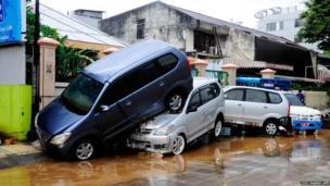 Cars are seen on top of each after being hit by flood waters in Manado