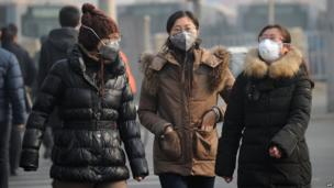 A group of women wear face masks as they make their way along a street in Beijing on January 16, 2014.