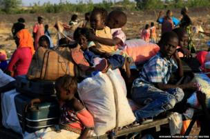 South Sudanese refugees wait at a border gate in Joda