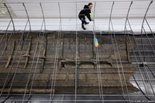 A conservationist at the British Museum cleans and prepares the metal frame of a forthcoming exhibition of the surviving timbers of the longest Viking warship