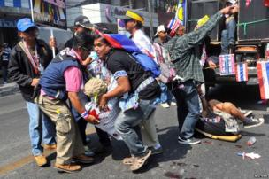 Anti-government protesters help a fellow protester injured in a grenade attack during a rally in Bangkok.