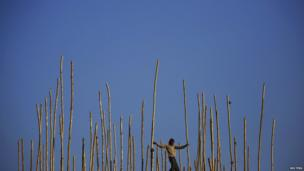 A migrant labourer from India balances himself as he walks on bamboo scaffolding while constructing the Vaishno Devi Temple, measuring 24 metres (79 feet) in height, at the premises of Pashupatinath Temple in Kathmandu, Nepal
