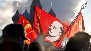 People carrying red flags with portraits of Soviet founder Vladimir Lenin