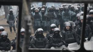 Photographed through a vehicle torched by protesters overnight, police officers block a street during unrest in central Kiev, Ukraine, Tuesday 21 January 2014
