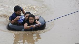 A family using an inflatable tyre tube to escape flooding.