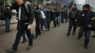 Opposition supporters, right, escort people believed to be government-hired thugs away from an opposition camp in central Kiev, Ukraine, Tuesday 21 January 2014