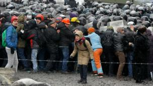 A woman (C, front) reacts as Interior Ministry members push pro-European protesters during a rally in Kiev on Wednesday