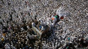 Mourners crowd around the vehicle carrying the body of their spiritual leader Syedna Mohammed Burhanuddin during his funeral procession in Mumbai