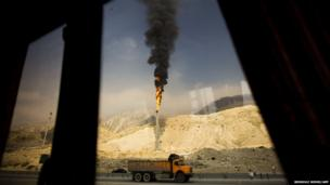 A gas flame is seen through a bus window in the South Pars gas field facilities in the southern Iranian port of Assaluyeh