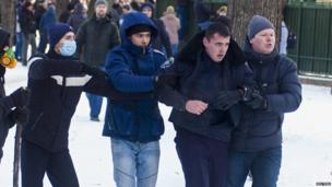 Anti-government protesters escort a policeman after disarming him near the regional administration headquarters in the central Ukrainian city of Dnipropetrovsk on Sunday