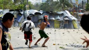 Residents throw stones and bottles at police shields in an area of Manila inhabited by squatters