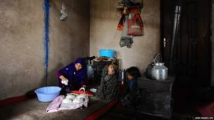 An Afghan mother makes bread for her children in Herat