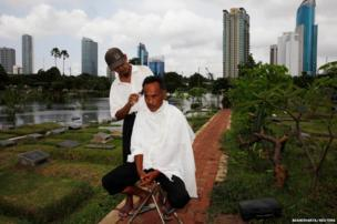 Cemetery worker Mohammad Udin has his hair cut by a mobile barber