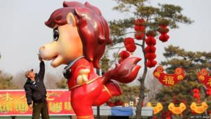 Worker putting the final touches on a cartoon horse in China