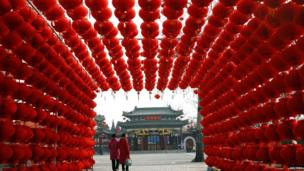 Visitors walk past red lantern decorations at Longtan park