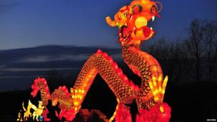 Tourists take a picture in front of a giant dragon lantern