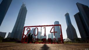 People walk past a 2014 installation at Lujiazui financial district of Pudong ahead of the Chinese lunar New Year in Shanghai.