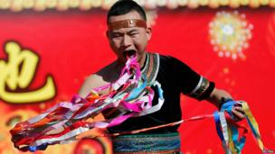 A man pulls ribbons from his mouth as he performs a feat of his strength during the opening of the Temple Fair for Chinese New Year celebrations at Ditan Park, also known as the Temple of Earth, in Beijing on 30 January