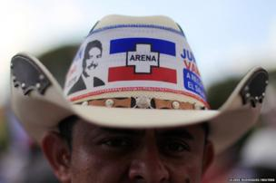 A supporter wears a hat with an image of Norman Quijano