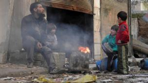 A man and children sit around a fire in the besieged area of Homs