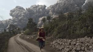 A villager runs as Mount Sinabung erupt at Sigarang-Garang village in Karo district, Indonesia's North Sumatra province, February 1