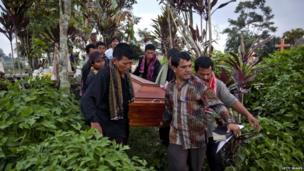 Relatives carry a coffin during the burial of a victim that was killed after being hit by pyroclastic smoke from the eruption of Mount Sinabung on 2 February 2014 in Suka village, Karo District, North Sumatra, Indonesia