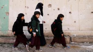 Children walk past the site of an explosion in Sanaa