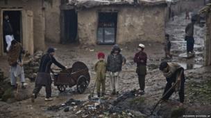 Men clear open sewage paths in Islamabad, Pakistan