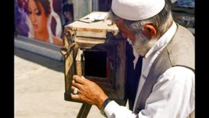 Mirzaman opening the back door of his camera to view the positive image.